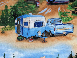 Close up of a blue and white vintage travel trailer and blue truck.