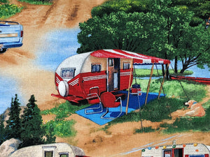 Close up of a red and white vintage travel trailer set up in a camping space.
