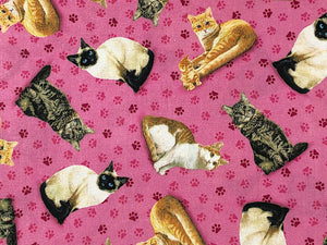 Close up of pink cotton fabric covered with cats and paw prints.