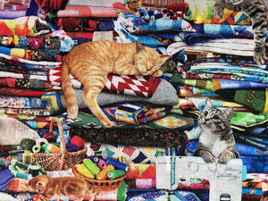 Close up of a cat sleeping on a pile of quilts.