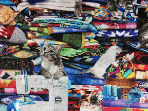 Close up of a cat laying over a sewing machine and a cat playing with sewing notions.
