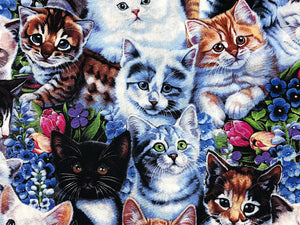 Close up of cotton fabric that is covered with kittens and flowers.