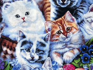 Close up of cotton fabric that is covered with kittens and flowers
