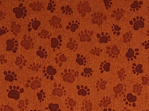Close up of brown paw prints on brown cotton fabric