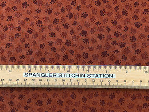 Ruler on brown cotton fabric that is covered in paw prints