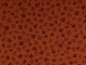 Cotton fabric with brown paw prints on a brown background