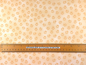 Ruler on fabric that is covered in paw prints