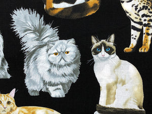Close up of black cotton fabric covered with cats.