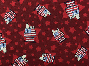 Close up of red cotton fabric with Snoopy laying on top of his Patriotic Flag house.