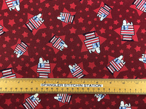 Ruler on red cotton fabric that has Snoopy laying on top of his patriotic flag house.