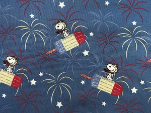 Close up of blue cotton fabric with Snoopy Flying on a red, white and blue popsicle.