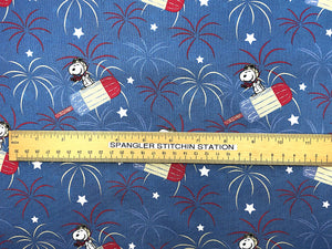 Ruler on blue cotton fabric that has Snoopy flying on a red, white and blue popsicle.