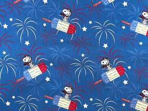 Blue cotton fabric covered with Snoopy flying on a red, white and blue popsicle.
