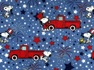 Close up of blue cotton fabric covered with red trucks and Snoopy and Woodstock celebrating independence day.
