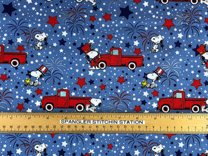 Ruler on blue cotton fabric that has Snoopy and Woodstock celebrating the 4th of July.