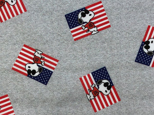 Close up of grey cotton fabric with Snoopy as Joe Cool in front of a USA flag.