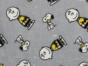 Close up of light grey fabric covered with Snoopy, Woodstock and Charlie Brown