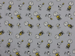 Light grey cotton fabric covered with Snoopy, Charlie Brown and Woodstock.