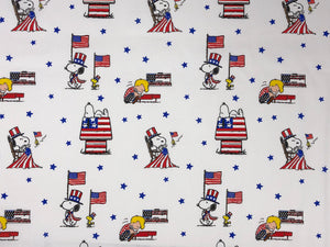 White cotton fabric covered with Snoopy, Woodstock and Schroeder.