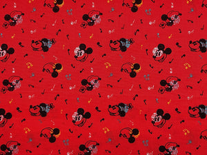 Red fabric covered with Mickey Mouse and music notes.