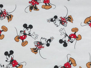 Close up of white cotton fabric covered with Mickey and Minnie Mouse