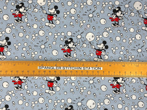 Ruler on light grey fabric showing the size of Mickey and Minnie Mouse.
