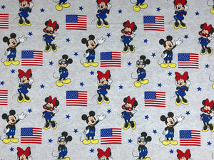 Grey cotton fabric covered with Patriotic Mickey and Minnie Mouse and USA flags.