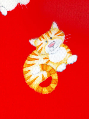 Close up of orange and white cat on a red background of cotton fabric