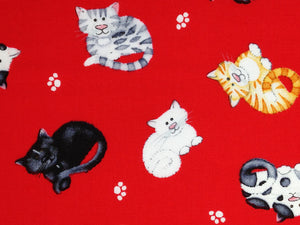 Cotton Fabric with a close up of cats on a red background with paw prints between the cats.