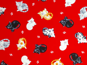 Red Cotton fabric covered with white, black and orange cats.