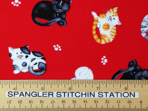 Ruler on fabric which is covered with cats on a red background.