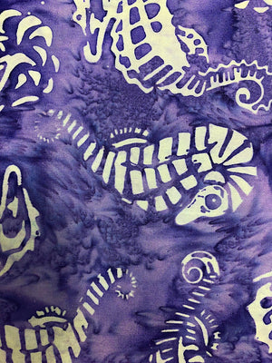 Close up of purple batik fabric that is covered with seahorses