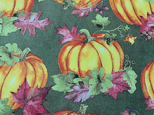 Close up of pumpkins and leaves on green cotton fabric.