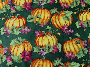 Green fabric covered with pumpkins and leaves.