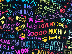 Close up of black cotton fabric covered with dog sayings such as woof, I Love my dog and more.