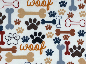 Close up of cream cotton fabric that is covered with dog bones and paw prints.
