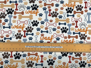 Ruler on cream cotton fabric that is covered with dog bones and paw prints and the word woof.