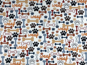 Cream cotton fabric covered with dog bones and paw prints.