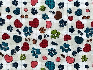 Close up of cotton fabric covered with paw prints and hearts.