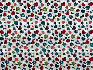 Cotton fabric covered with hearts and paw prints.