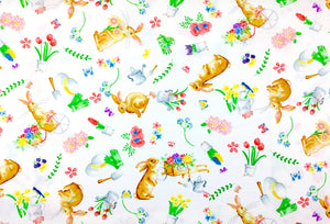 White cotton fabric covered with bunnies, watering cans, tulips, hats, gloves and more.