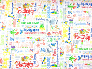 White cotton fabric covered in spring words such as butterfly and garden. There are also small pots of flowers and watering cans.