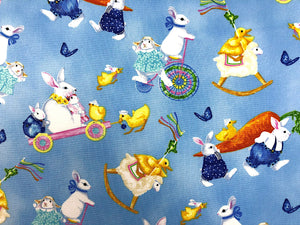 Close up of blue cotton fabric covered with bunnies, chicks and butterflies.