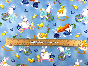 Ruler on blue cotton fabric covered with Bunnies, chicks and butterflies