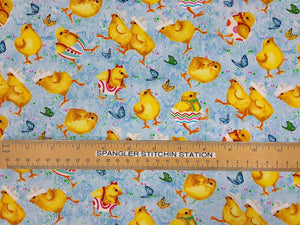 Ruler on blue fabric with Easter chicks and butterflies scattered throughout