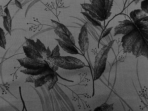 Close up of grey fabric covered with leaves.