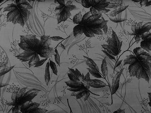 Grey cotton fabric covered with leaves.
