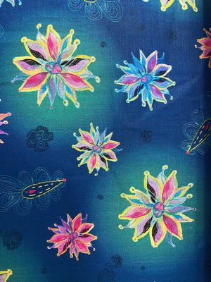 Close up of blue cotton fabric that is covered in flowers.