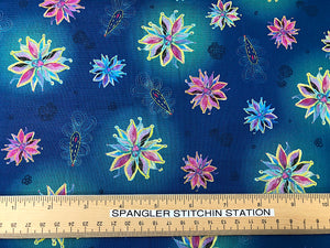 Ruler on blue cotton fabric that is covered in flowers.