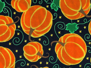 Close up of black cotton fabric that is covered with orange pumpkins, green swirls and leaves and yellow stars.